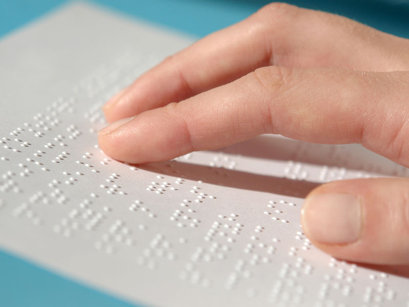 28668779 - blind woman reading text in braille
