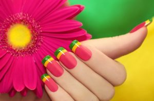 25996261 - multicolored manicure with pink,yellow and green lacquer against the background with gerberas