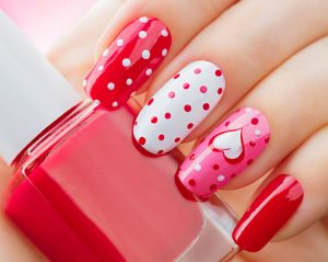 50758747 - valentines day holiday style bright manicure with painted hearts and polka dots